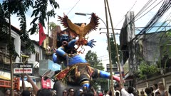villagers moving an ogoh-ogoh statue into position for the new year parade at kuta on bali, indonesia