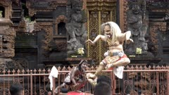 a small ogoh-ogoh statue and balinese boys at kuta beach in bali
