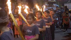 hindu girls with burning torches on a kuta street during the nyepi parade in bali, indonesia