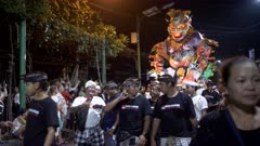a night shot of villagers carrying an ogoh-ogoh along a kuta street in bali during the hindu new year parade