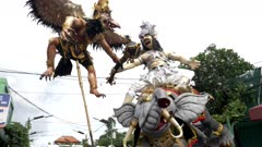 tracking shot of an ogoh-ogoh being moved on a kuta street of bali for a nyepi parade