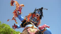 a low angle shot of an ogoh-ogoh statue with a garuda at kuta beach in bali, indonesia