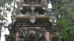 tilt down shot of an elaborately carved temple gate at tirta empul temple (holy water spring) on bali, indonesia