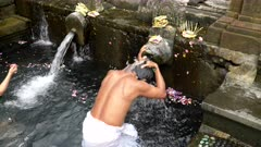 high view of two hindu worshipers bathing under the holy water spring fountains at tirta empul temple on bali, indonesia