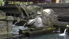 an elephant statue and the holy spring fountains at tirta empul temple on bali, indonesia