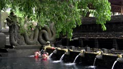 wide view of an elephant statue and two female worshipers bathing under the holy spring fountains at tirta empul temple on bali, indonesia