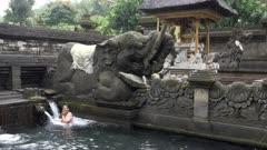 woman bathing below an elephant statue at tirta empul temple on bali, indonesia