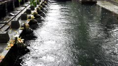 rain storm at the holy spring fountains at tirta empul temple on bali, indonesia