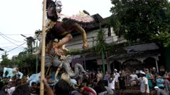 side view of hindu men moving an ogoh-ogoh statue on a street in preparation for the nyepi (new year) parade at kuta on the indonesian island of bali