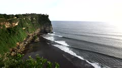 an afternoon shot of the cliffs and surf at uluwatu temple on the island of bali, indonesia