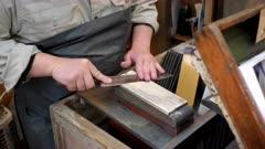 a master craftsman sharpening a knife by hand at tsukiji market in tokyo, japan