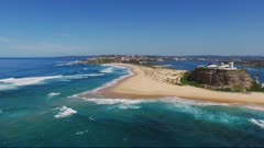 a wide angle aerial drone shot flying toward nobbys head in newcastle, australia