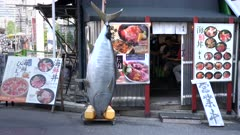 model of a tuna in front of a sushi restaurant at tsukiji fish market in tokyo, japan