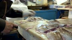 a workers trims fish fillets at tsukiji market in tokyo, japan