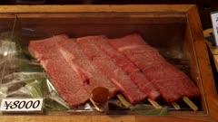 close up of raw wagyuu beef skewers at tsukiji fish market in tokyo, japan