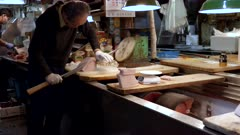 a worker uses a long knife to cut tuna portion and then weighs it at tsukiji market in tokyo