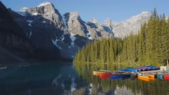 tilt up shot of moraine lake and canoes at a dock in banff national park, canada