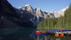 a morning shot of canoes tied up to a dock at moraine lake in banff national park in canada