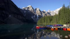 a wide view of moraine lake and canoes on a sunny summer morning in banff national park, canada