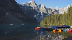 a morning shot of tourists paddling a canoe on moraine lake in banff national park, canada