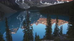 a sunrise tilt up view of a calm moraine lake at banff national park in canada