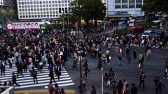 a high angle shot of the busy pedestrian crossing at shibuya in tokyo, japan
