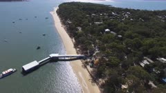 an aerial view of a ferry arriving at coochiemudlo island in morton bay of queensland, australia