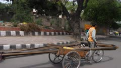 a 4K 60p clip of man on bicycle carrying steel reinforcement bars in delhi, india