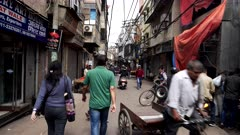 a gimbal steadicam clip walking along a chandni chowk street in old delhi, india