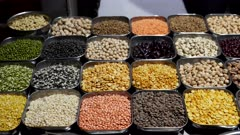 a panning shot of a variety of pulses for sale at the chandni chowk spice market in old delhi, india