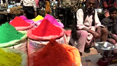 a close view of vendors waiting beside bags of colorful holi powder at the spice market of chandni chowk in old delhi, india