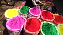 pan of large bags of bright colored powder for holi at the spice market of chandni chowk in old delhi, india