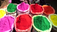 zoom in on vividly colored bags of holi powder at the spice market of chandni chowk in old delhi, india