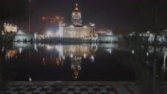 night shot of gurudwara bangla sahib sikh temple and the sacred pool in delhi, india