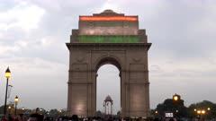 close gimbal steadicam clip walking towards india gate illuminated with indian flag at dusk in new delhi, india