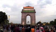 gimbal steadicam clip walking through crowds towards india gate, illuminated with indian flag, at dusk in new delhi
