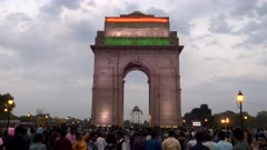 a wide gimbal steadicam clip walking towards india gate with flag at dusk in delhi, india