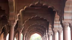 a close up gimbal clip walking under beautiful arches at red fort in old delhi india