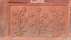 a decorative floral carving on a stone wall at red fort in old delhi, india- 4K 60p