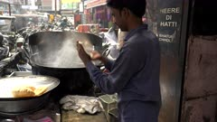 cook flattens poori bread by hand and puts in oil at amritsar, india