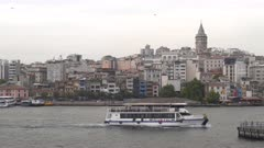 a tour ferry with galata tower in the background at istanbul, turkey