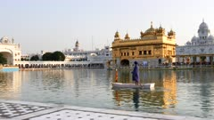 a guard paddles a boat around the pool at golden temple in amritsar, india