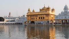 a close view of the golden temple and its reflection in the surrounding pool at amritsar, india