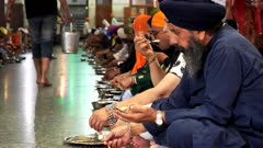 a sikh man eating in golden temple's free food hall at amritsar, india