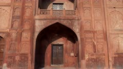 a tilt up shot of the doorway and window of a building at red fort in old delhi, india