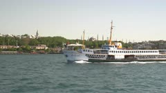 a ferry sailing with the hagia sophia mosque in the distance at istanbul, turkey
