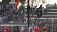 the indian and pakistan flags being taken down at the wagah border in amritsar, india