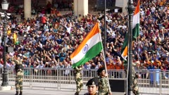 indian flags being waved by guards at wagah border in amritsar, india