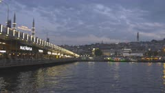 a panning shot at dusk from galata bridge to rustem pasha mosque in istanbul, turkey