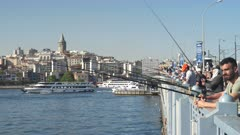 fishermen on galata bridge with galata tower and boats in the background at istanbul, turkey